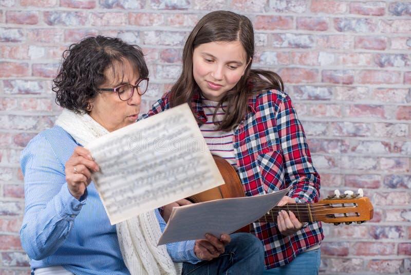 Giovane adolescente che impara giocare la chitarra con il suo insegnante immagine stock libera da diritti
