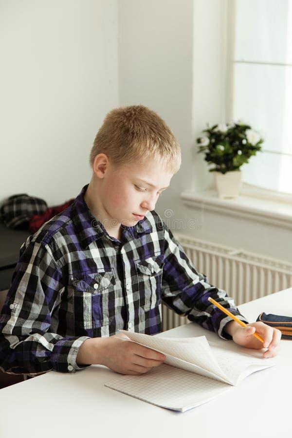 Giovane adolescente che si siede allo scrittorio che fa compito immagini stock libere da diritti