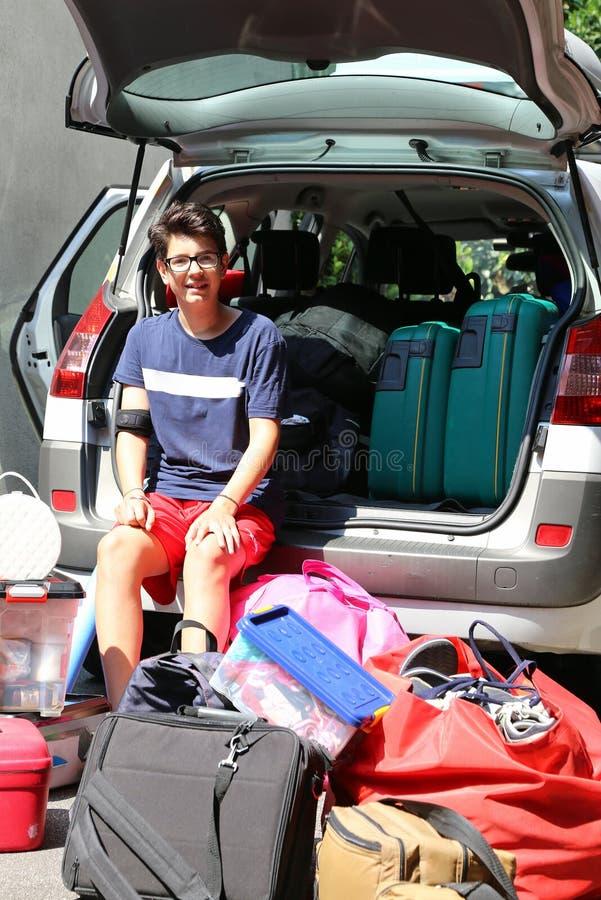 Giovane adolescente che si siede sull'automobile con i vetri fotografie stock