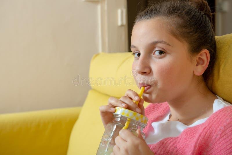 Giovane adolescente che si siede in un succo d'arancia bevente del sofà giallo immagine stock