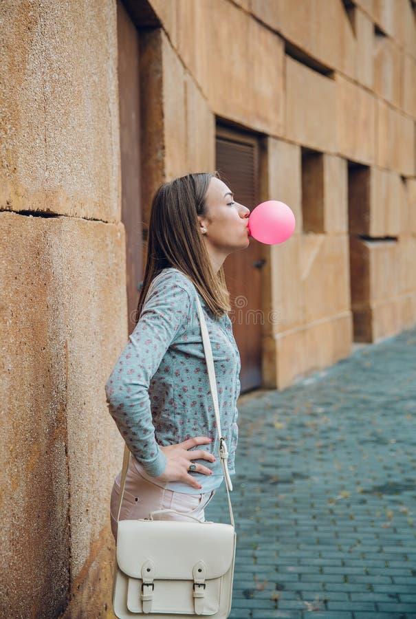 Giovane adolescente che soffia di gomma da masticare rosa fotografie stock