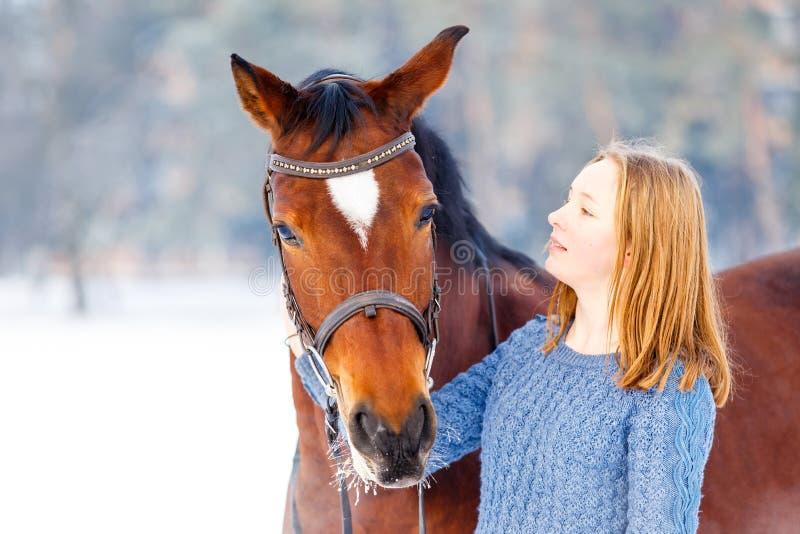 Giovane adolescente con il cavallo di baia nel parco di inverno immagini stock libere da diritti