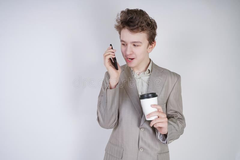 Giovane adolescente con le emozioni sorprese in vestiti grigi di affari che stanno con la tazza di caff? della carta e del telefo immagini stock