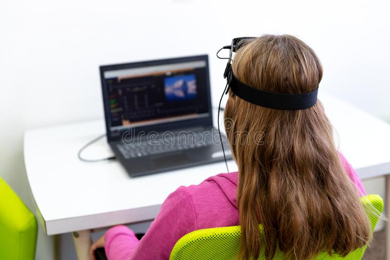 Giovane adolescente durante la sessione del neurofeedback di elettroencefalogramma Concetto di elettroencefalografia Vista poster immagini stock libere da diritti