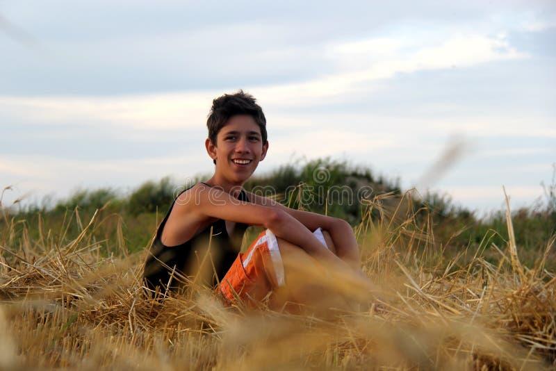 Giovane adolescente felice che si siede al giacimento ed a sorridere del fieno fotografia stock