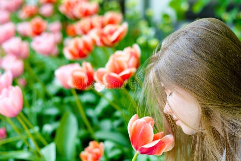 Giovane adolescente felice con un tulipano fotografia stock libera da diritti