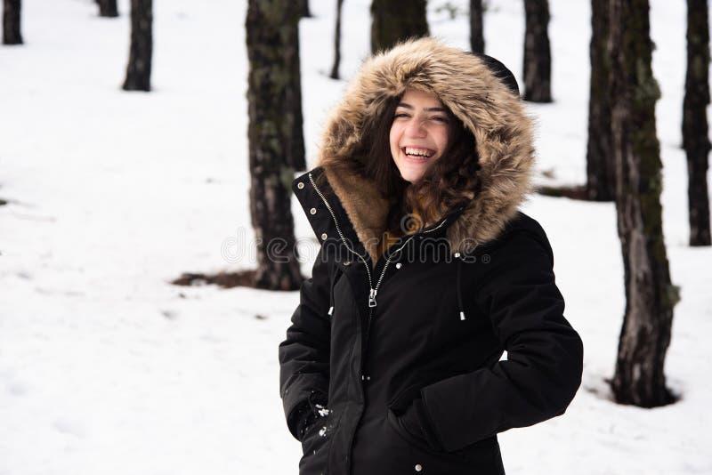Giovane adolescente felice e bella vestita d'inverno con la neve e sorridente immagine stock libera da diritti