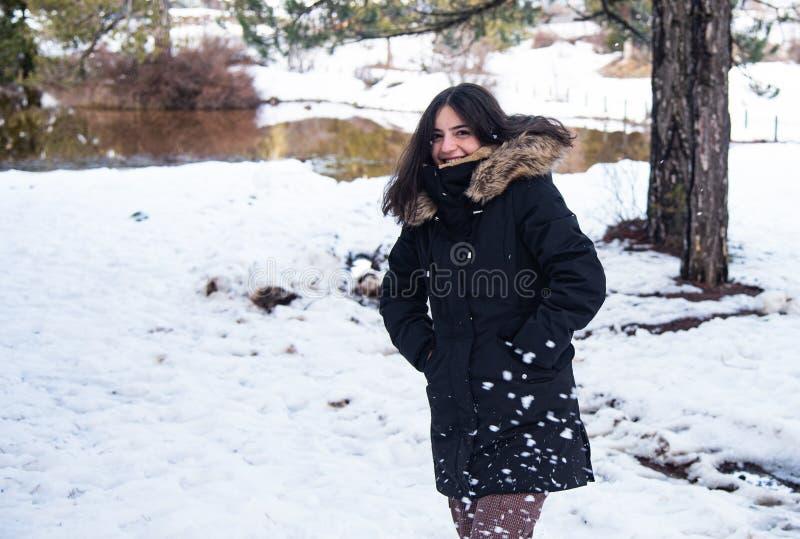 Giovane adolescente felice e bella vestita d'inverno con la neve e sorridente fotografia stock
