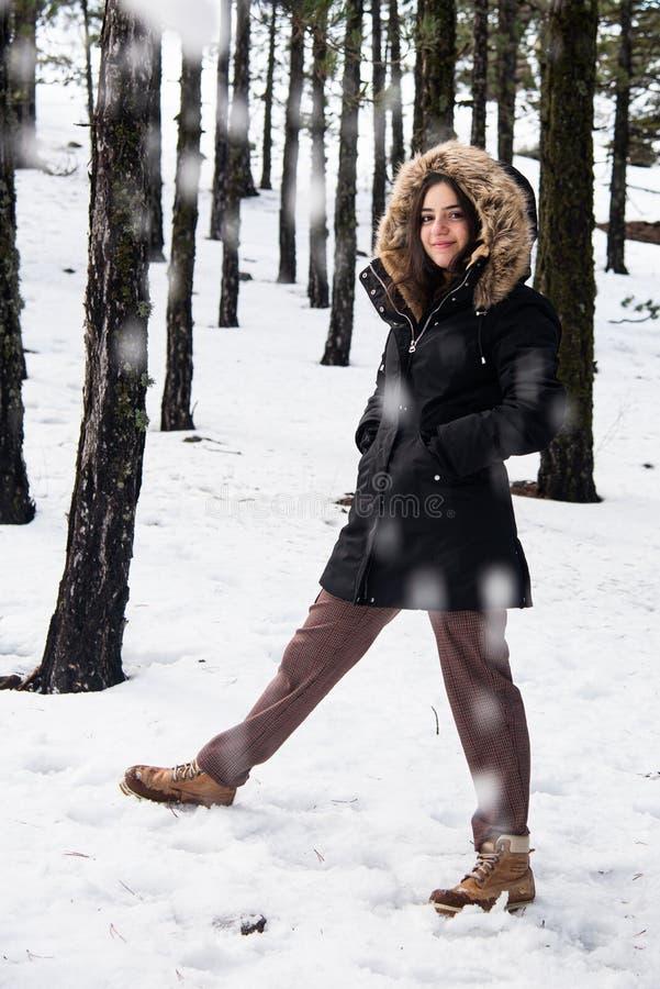 Giovane adolescente felice e bella vestita d'inverno con la neve e sorridente fotografie stock