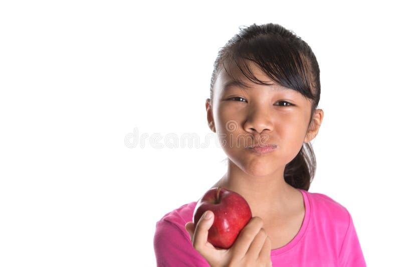 Giovane adolescente malese asiatico che mangia Apple rosso IX fotografie stock libere da diritti