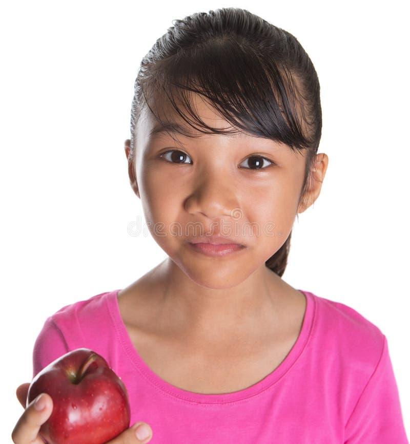 Giovane adolescente malese asiatico che mangia Apple rosso XI fotografia stock libera da diritti
