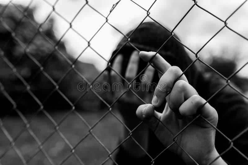 Giovane adolescente non identificabile che tiene il giardino metallico all'istituto correttivo, coprente il fronte dei hes fotografia stock libera da diritti