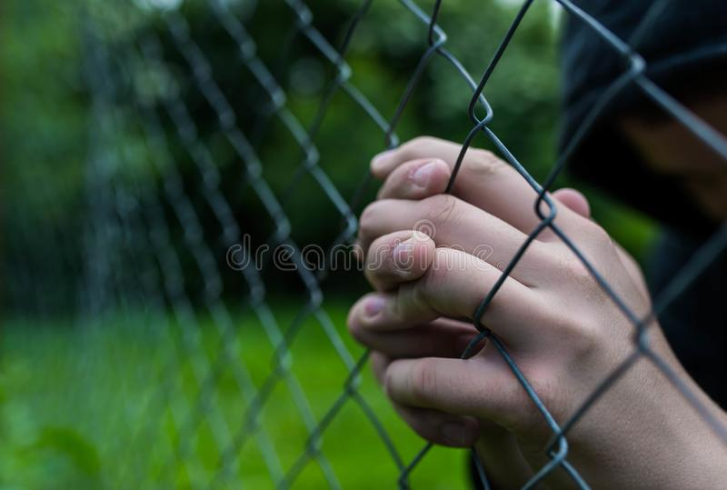 Giovane adolescente non identificabile che tiene il giardino metallico che prega all'istituto correttivo fotografia stock