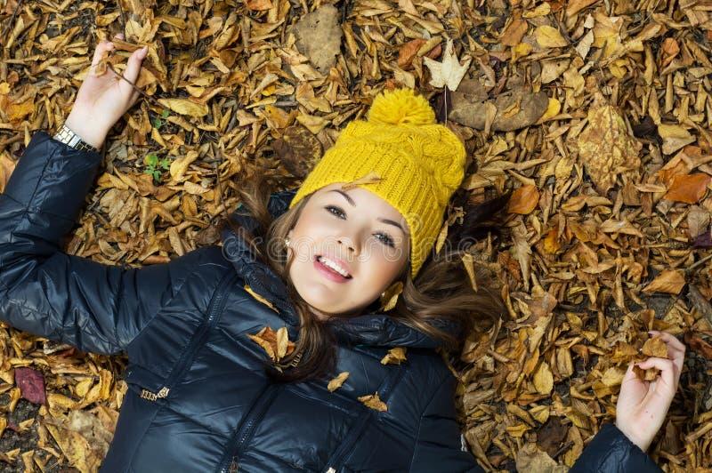 Giovane adolescente sorridente che si trova nelle foglie di autunno immagini stock libere da diritti
