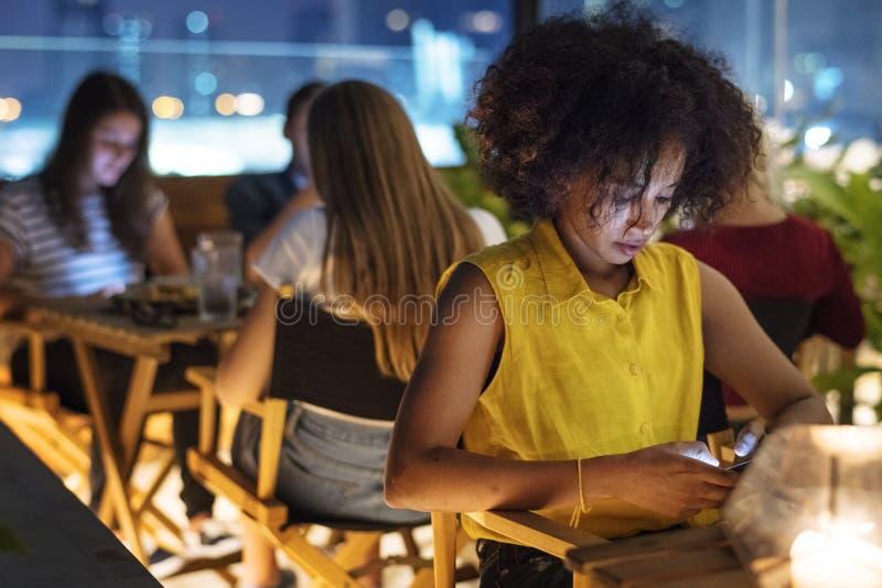 Giovane adulto ad una data della cena facendo uso di un concep di dipendenza dello smartphone immagine stock libera da diritti