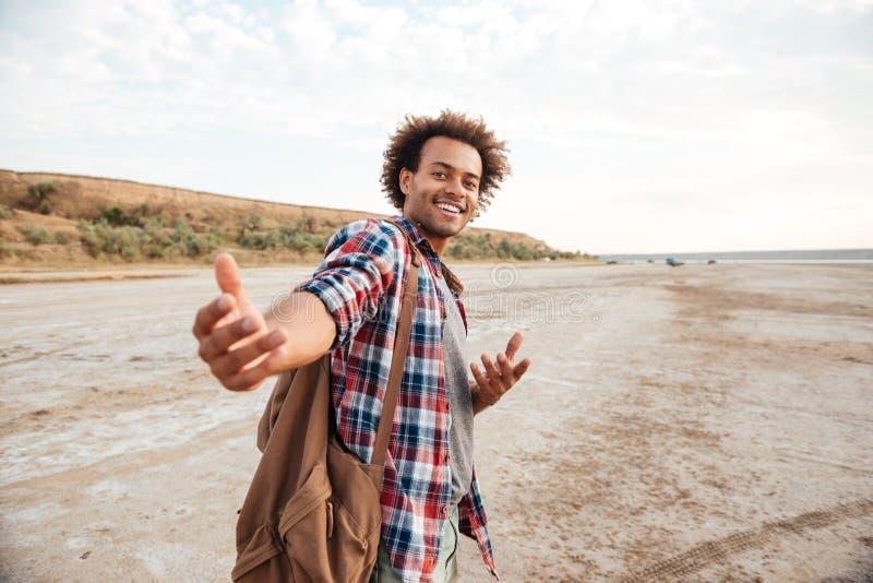 Giovane africano felice che vi invita a andare con lui immagine stock libera da diritti