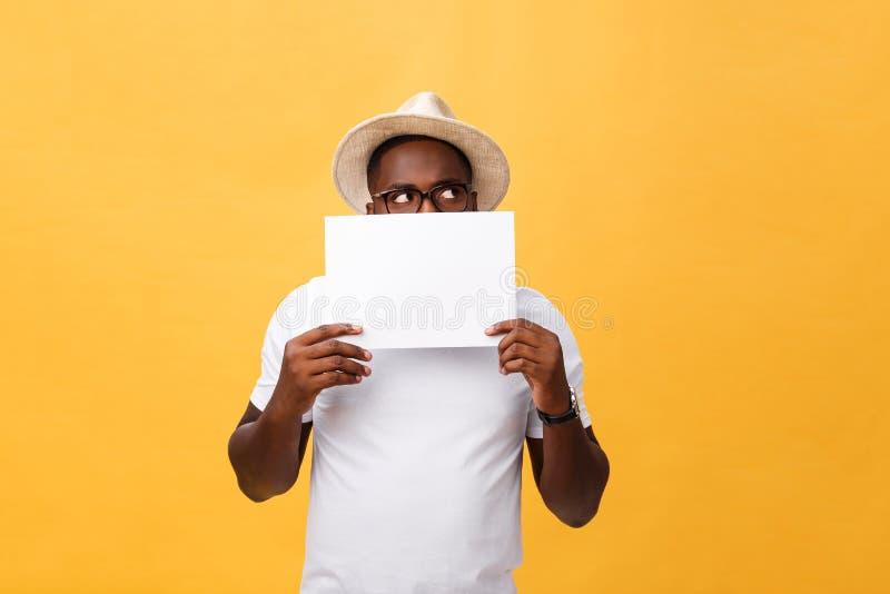 Giovane afroamericano felice che si nasconde dietro una carta in bianco, isolata su fondo giallo fotografie stock libere da diritti