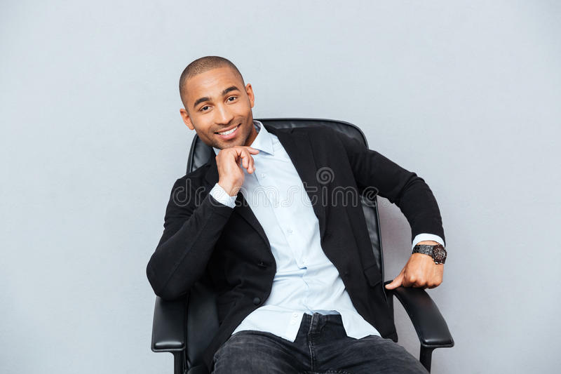 Giovane afroamericano sorridente sicuro che si siede nella sedia dell'ufficio fotografia stock libera da diritti