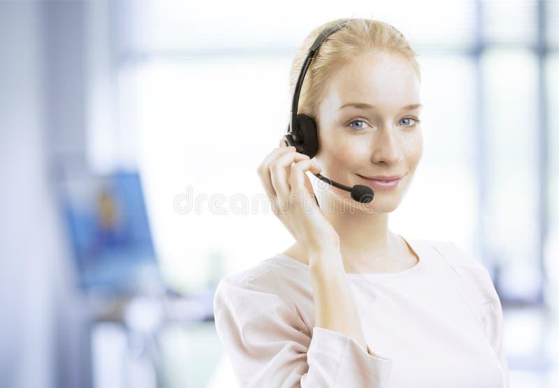 Giovane agente femminile sorridente di servizio di assistenza al cliente con la cuffia avricolare immagini stock libere da diritti