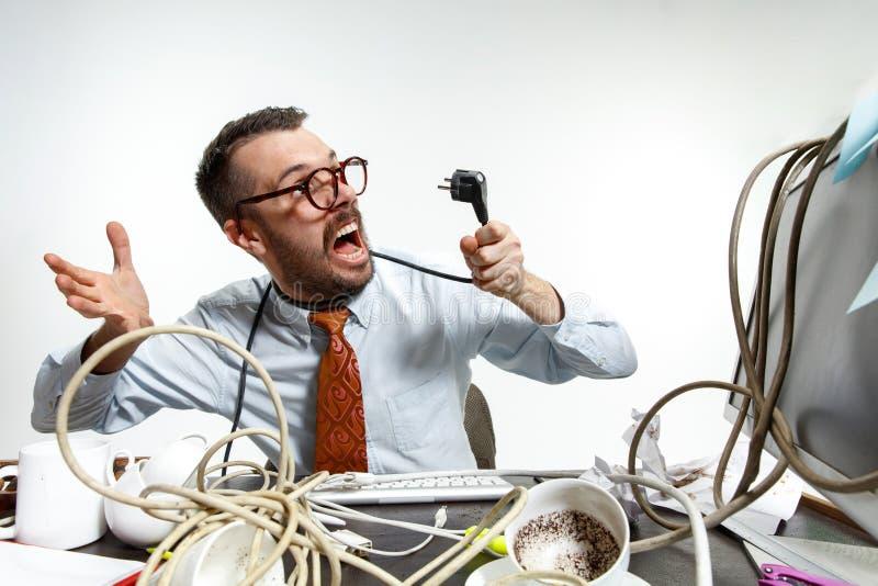 Giovane aggrovigliato in cavi sul posto di lavoro fotografia stock libera da diritti