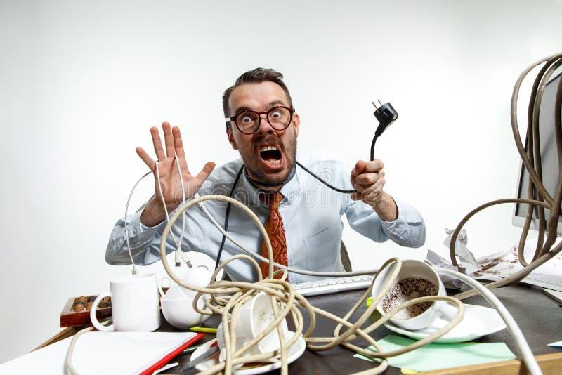 Giovane aggrovigliato in cavi sul posto di lavoro fotografie stock