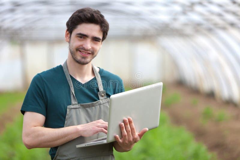 Giovane agricoltore di affari che lavora al suo computer portatile immagine stock libera da diritti