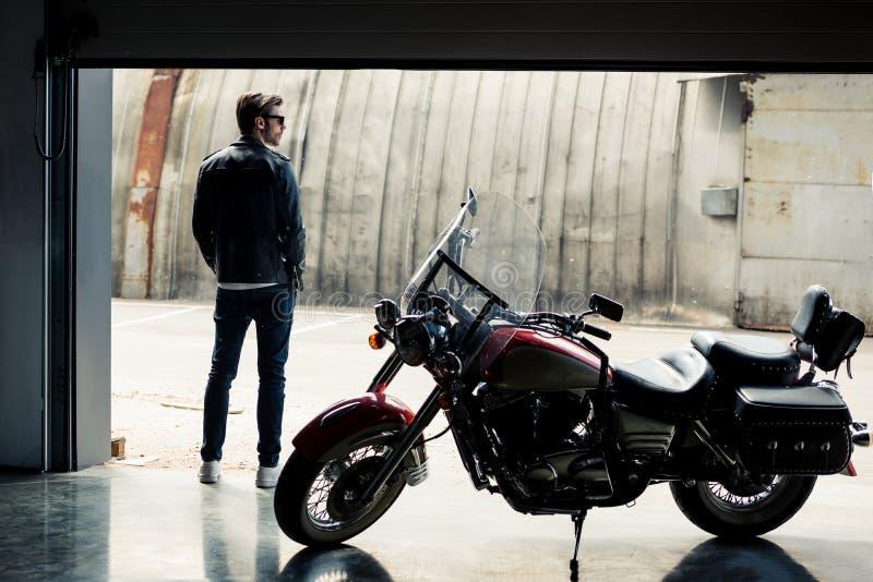 Giovane alla moda in bomber che sta motocicletta vicina e distogliere lo sguardo fotografie stock libere da diritti