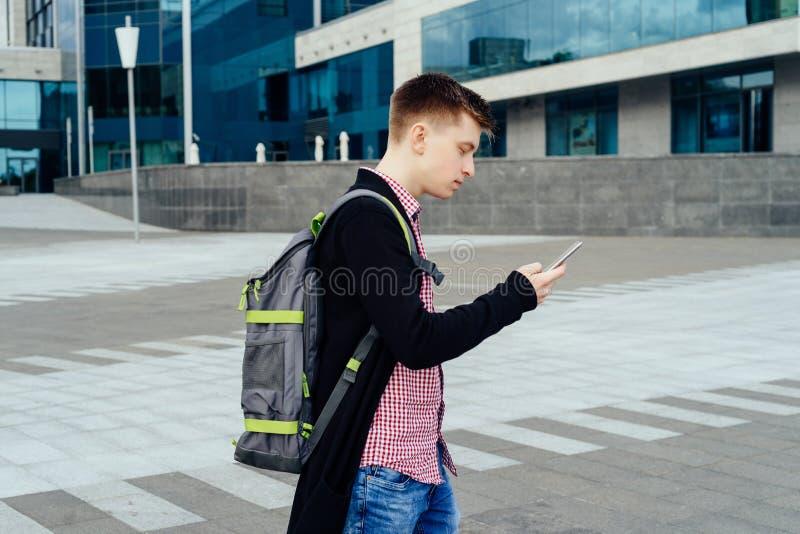 Giovane alla moda in camicia di plaid con lo zaino che cammina nella città immagini stock libere da diritti