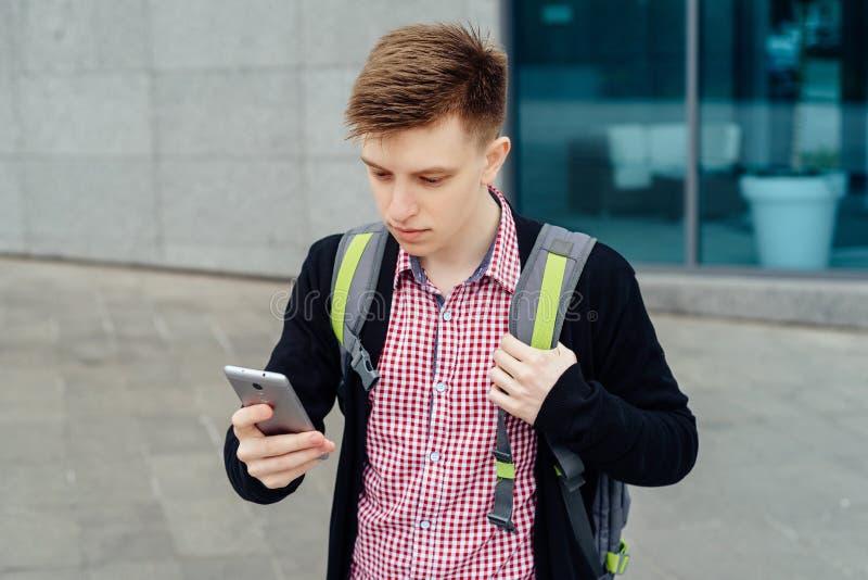 Giovane alla moda in camicia di plaid con lo zaino che cammina nella città immagine stock