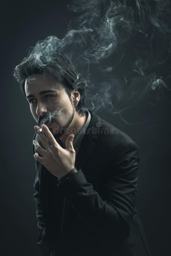 Giovane alla moda che fuma una sigaretta immagine stock libera da diritti
