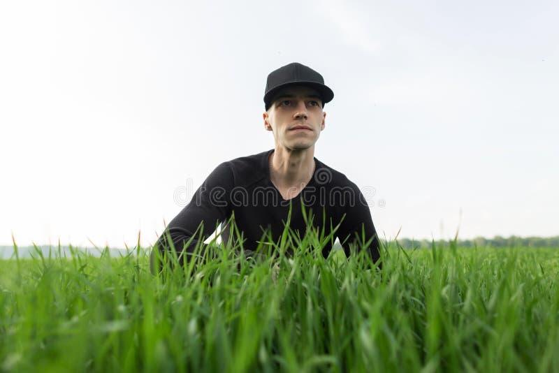 Giovane alla moda in una camicia nera nei resti d'avanguardia neri di un cappuccio che si siedono nell'erba verde nel campo Tiran immagine stock