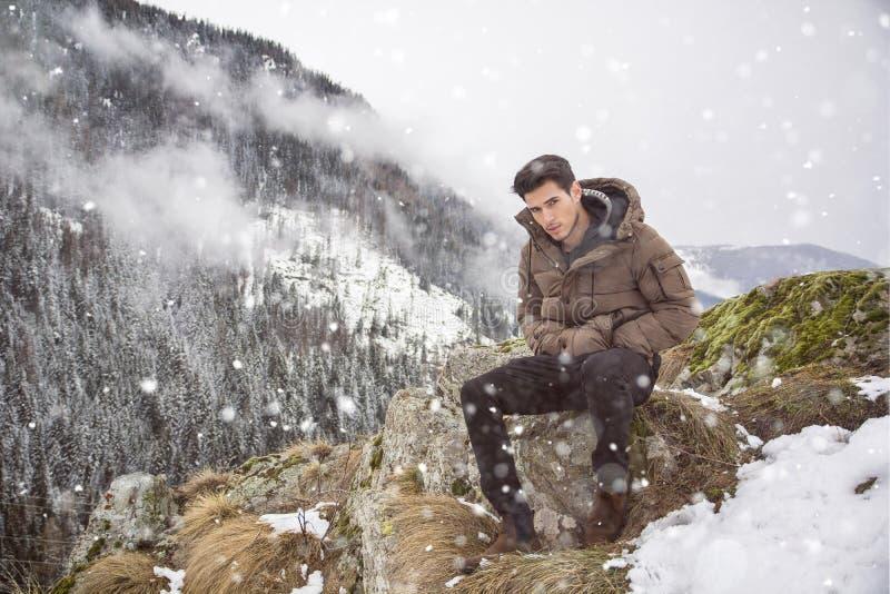 Giovane alla montagna che si siede sotto la neve fotografie stock libere da diritti