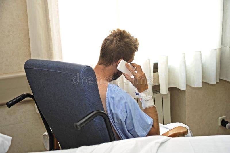 Giovane alla stanza di ospedale che porta i pigiami pazienti che si siedono dalla finestra che parla sul telefono cellulare fotografie stock libere da diritti