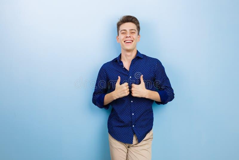 Giovane allegro con capelli scuri che portano camicia blu, mostranti i pollici sul gesto, sorridenti ampiamente ed esaminanti mac fotografie stock
