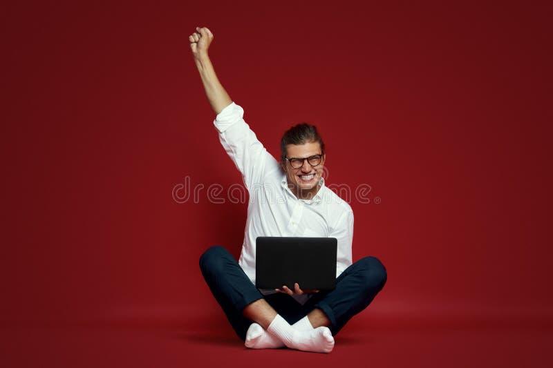 Giovane allegro con gli occhiali che portano camicia bianca che si siede su un pavimento e su una celebrazione isolati sopra fond fotografie stock