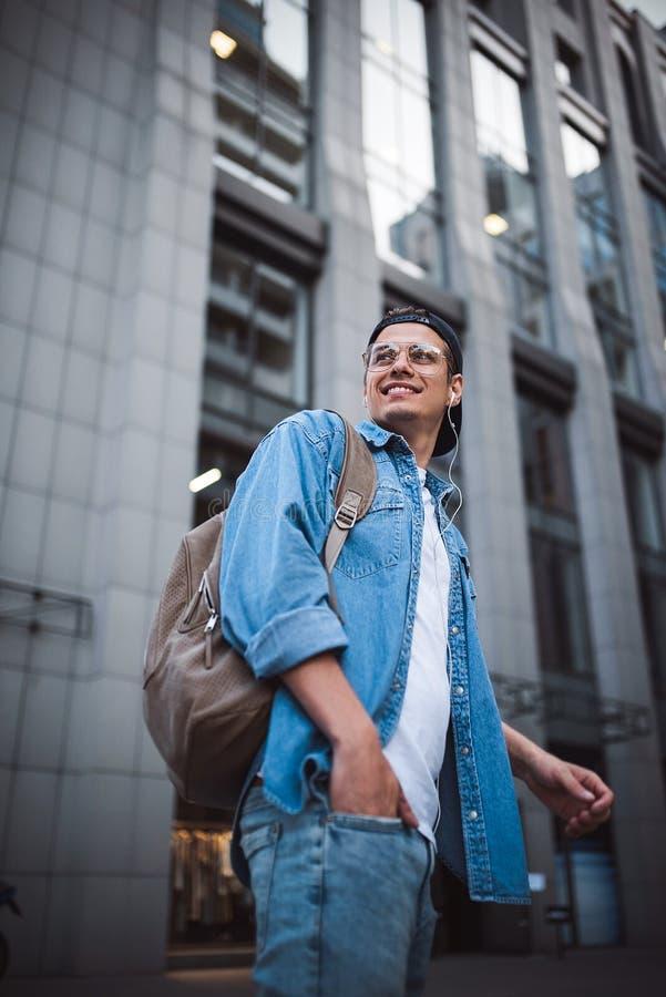 Giovane allegro con lo zaino che gode della passeggiata la città fotografie stock