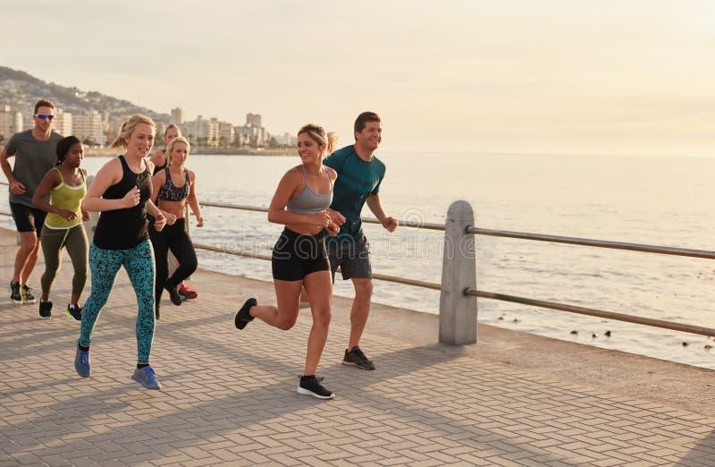 Giovane allenamento dei corridori lungo una passeggiata della spiaggia fotografia stock libera da diritti