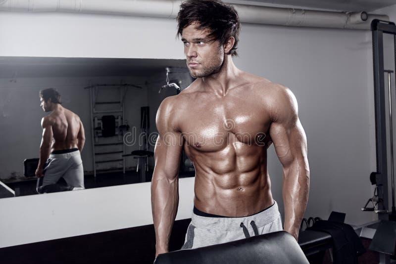 Giovane allenamento sexy muscolare dell'uomo in palestra immagini stock libere da diritti