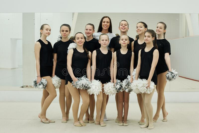 Giovane allenatore con una squadra di ragazze cheerleader immagine stock