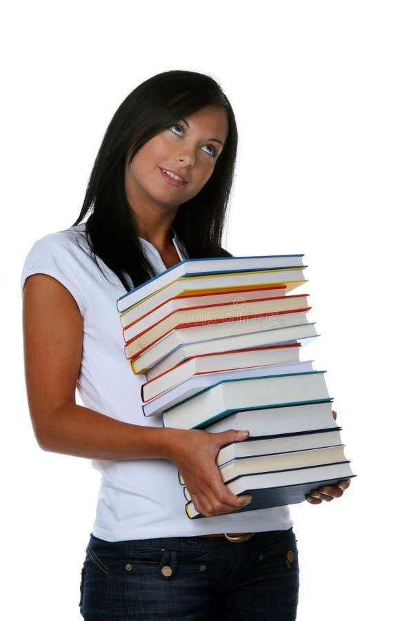 Giovane allievo con una pila di libri immagini stock libere da diritti