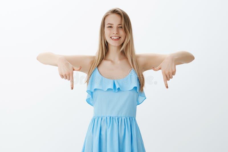 Giovane amica attraente piacevole e felice con capelli biondi naturali in vestito blu che indica giù e che sorride largamente immagine stock