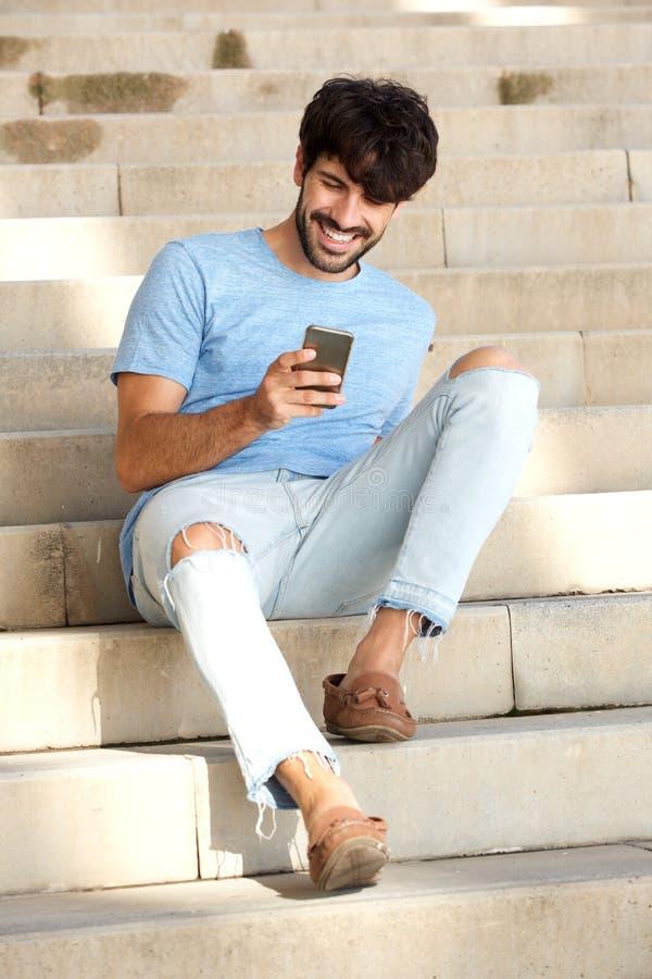 Giovane amichevole che si siede sui punti che esaminano telefono cellulare fotografie stock libere da diritti
