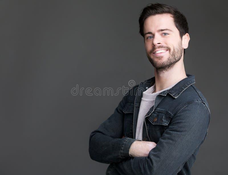 Giovane amichevole che sorride con le armi attraversate fotografie stock