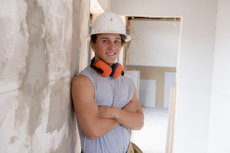 Giovane apprendista attraente e sicuro di lavoro del costruttore e del costruttore che impara e che lavora al collare blu del sit fotografie stock