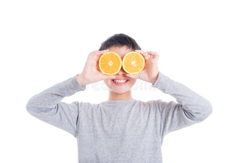 Giovane arancia asiatica e sorrisi della tenuta del ragazzo fotografia stock
