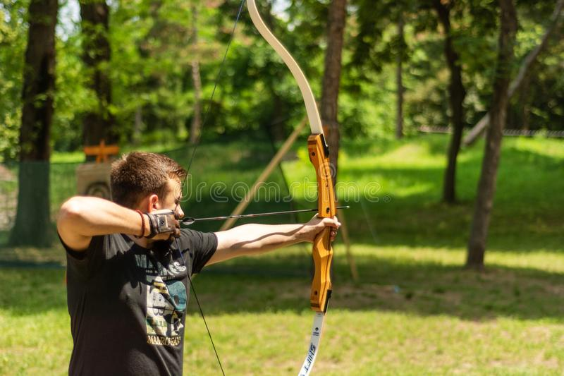 Giovane arcere con la freccia del tiro dell'arco nella foresta sul festival e sul torneo del cavaliere fotografie stock