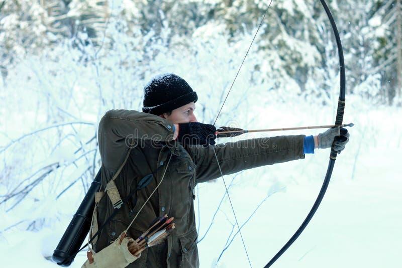 Giovane arcere nella foresta della neve di inverno immagine stock libera da diritti