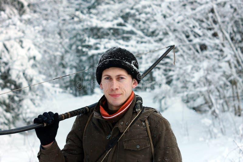 Giovane arcere nella foresta della neve di inverno immagine stock
