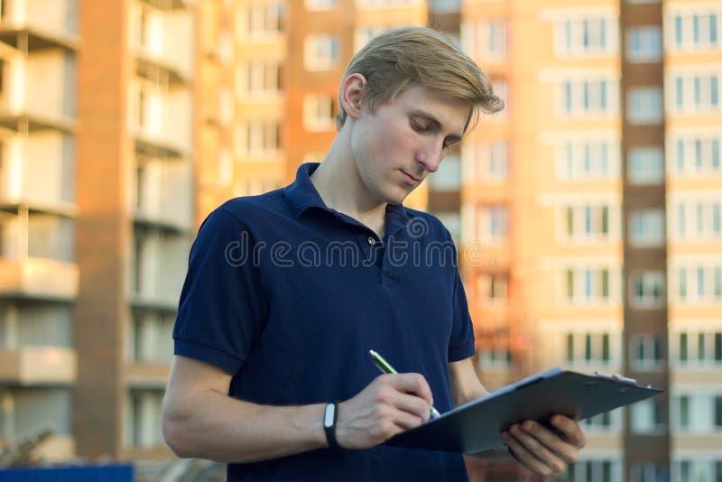Giovane architetto o ingegnere che controlla un piano di costruzione sul sito fotografia stock libera da diritti