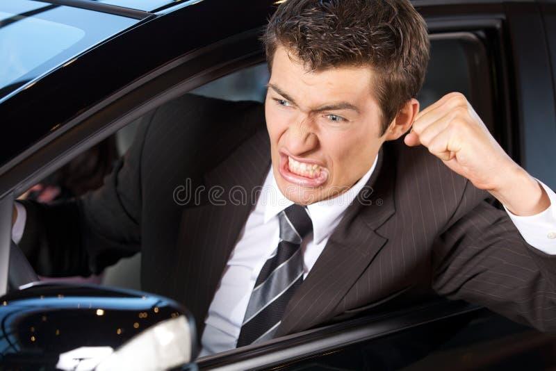 Giovane arrabbiato che serra il suo pugno, sedentesi in nuova automobile immagine stock
